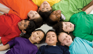 Kids sitting in a circle wearing colourful t-shirts